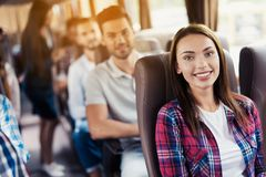 Женщина представляя на шине Она сидит и усмехается Вокруг ее сидите другие пассажиры Стоковая Фотография RF