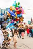 Женщина представляя с гелием раздувает на Oktoberfest Стоковая Фотография