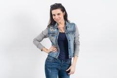 Женщина представляя в джинсах на белой стене Стоковые Фотографии RF