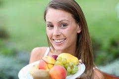 Женщина представляя плиту плодоовощей Стоковые Изображения RF