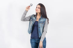 Женщина представляя с увеличителем на белой стене Стоковое Фото