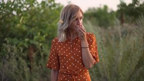 Женщина привлекательного hippie потехи белокурая есть яблоко в поле на заходе солнца, имеющ полезного время работы outdoors видеоматериал