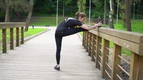 Женщина привлекательных детенышей подходящая протягивая ее ноги на деревянном мосте в парке после бега делать женщину тренировок  акции видеоматериалы