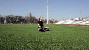 Женщина привлекательного молодого active подходящая делает йогу на траве огромного стадиона зеленой размышляя штилев наслаждающся видеоматериал