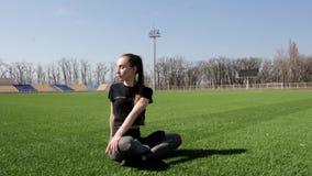 Женщина привлекательного молодого active подходящая делает представление простирания йоги на траву огромного стадиона зеленую раз сток-видео