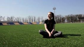 Женщина привлекательного молодого active подходящая сидя на огромный усмехаться зеленой травы стадиона смеясь над наслаждающся те акции видеоматериалы