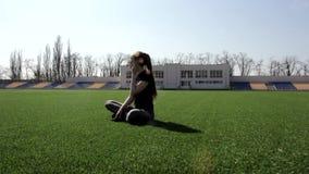 Женщина привлекательного молодого active подходящая сидя на траве огромного стадиона зеленой размышляя штилев наслаждающся теплым сток-видео