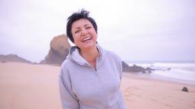Женщина привлекательного active зрелая бежать вдоль пляжа океана и усмехаясь на камере видеоматериал