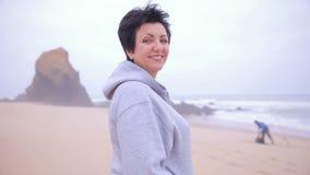 Женщина привлекательного active зрелая стоя на пляже океана и усмехаясь на камере видеоматериал
