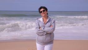 Женщина привлекательного active зрелая стоя на пляже океана и усмехаясь на камере сток-видео