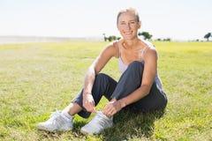 Женщина пригонки зрелая связывая ее шнурок на траве Стоковые Изображения
