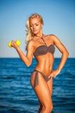 Женщина пригодности разрабатывая на пляже в лете Стоковое Изображение