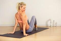 Женщина пригодности сидя на циновке Стоковые Изображения RF