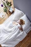 Женщина прижимаясь в кровати Стоковое Фото
