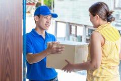 Женщина признавая поставку картонных коробок от работника доставляющего покупки на дом Стоковое фото RF