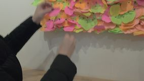 Женщина прикалывая кусок бумаги с сердцем на доску желания сток-видео
