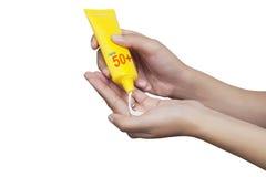 Женщина прикладывая солнцезащитный крем на ее изоляте руки на белой предпосылке стоковые изображения