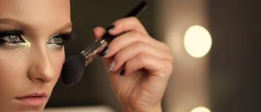 Женщина прикладывая сухое косметическое tonal учреждение на стороне используя щетку состава стоковые фотографии rf