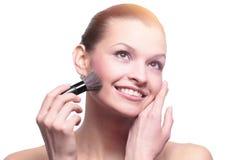 Женщина прикладывая сухое косметическое tonal учреждение на стороне используя m стоковые изображения rf
