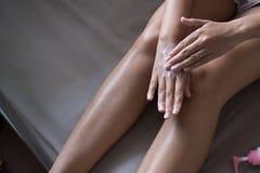 Женщина прикладывая moisturizing сливк на ее руках, концепции здоровой и коже стоковые фото