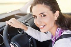 Женщина прикрепляя ремень безопасности в ее автомобиле стоковые изображения rf