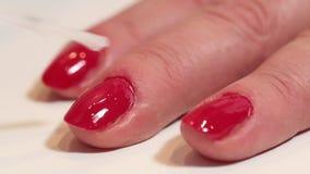 Женщина прикладывает прозрачный маникюр над красными ногтями сток-видео