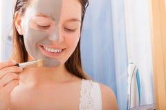 Женщина прикладывая маску ухода за лицом грязи Стоковые Фотографии RF