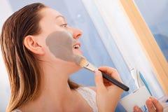 Женщина прикладывая маску ухода за лицом грязи Стоковое фото RF