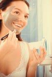 Женщина прикладывая маску ухода за лицом грязи Стоковая Фотография