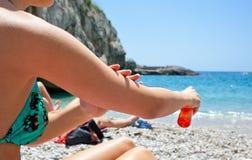 Женщина прикладывая масло лосьона suntan к ее телу стоковая фотография rf
