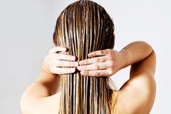 Женщина прикладывая проводник волос Изолировано на белизне Стоковое Фото