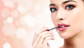 Женщина прикладывая состав губ с косметической щеткой Стоковая Фотография RF