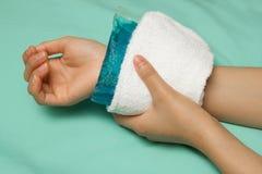 Женщина прикладывая холодный пакет на вздутом ушибая запястье руки стоковое изображение rf