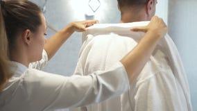 Женщина принимает белое пальто от взрослого человека акции видеоматериалы