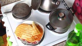 Женщина принимает вне готовый торт от утюга waffle Он кладет тесто в утюг waffle и закрывает его видеоматериал