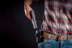 Женщина принимает вне пистолет от кобуры стоковое фото rf