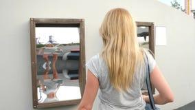 Женщина принимает его отражение в ложном зеркале на камере путешествие образа жизни она смеется над и дурачок 4K движение медленн сток-видео