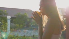 Женщина принимает испаряясь горячие чашку чаю или кофе на террасе и выпивать ее видеоматериал
