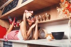 Женщина принимает остатки на кухне стоковые изображения
