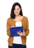Женщина принимает примечание на доске сзажимом для бумаги стоковые фото