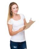 Женщина принимает примечание на доске сзажимом для бумаги стоковое фото rf