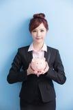 Женщина принимает розовую копилку стоковые изображения rf