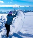 Женщина принимает снег порошка в ее руках и бросает ее в воздухе стоковое фото