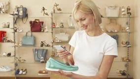 Женщина принимает фото ботинка в обувном магазине стоковые фото