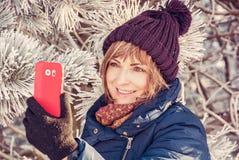 Женщина принимает фото selfie в зиме outdoors стоковая фотография