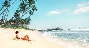 Женщина принимает sunbath на тропическом пляже Стоковое Изображение RF