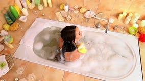 Женщина принимая ванну и мытье взваливают на плечи на пену в ее ванной комнате видеоматериал