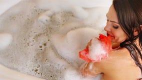 Женщина принимая ванну и мытье взваливают на плечи на пену в ее ванной комнате акции видеоматериалы