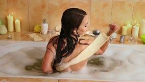 Женщина принимая ванну и мытье назад на пену в ее ванной комнате акции видеоматериалы