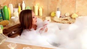 Женщина принимая ванну и дуя на пене в ее ванной комнате видеоматериал